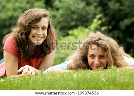 Smiling teenagers best friends lying on a grass in a park
