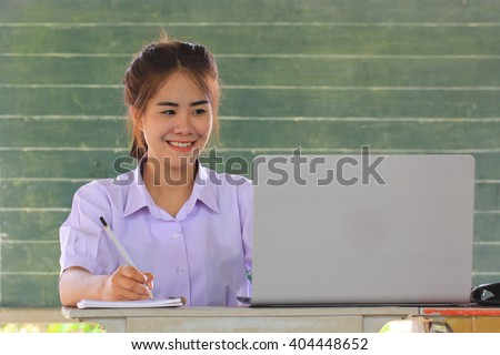 Smiling thai young women student looking at her notebook
