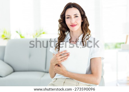 Smiling therapist holding her clipboard on white background - stock photo