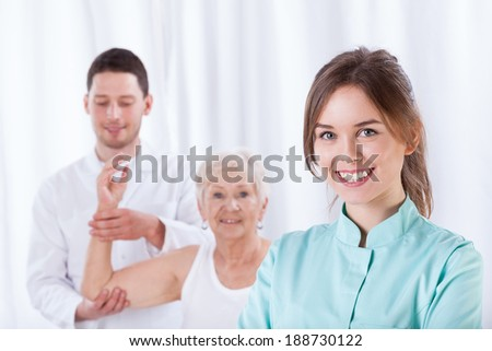 Smiling therapist standing in front of exercising elderly patient - stock photo