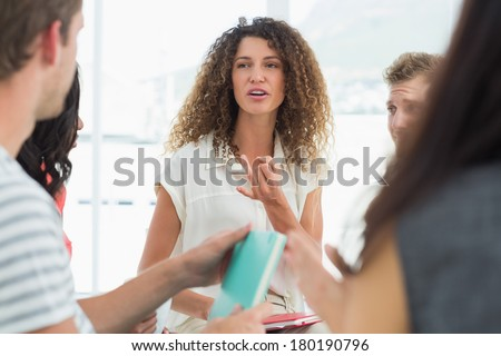 Smiling therapist talking with a rehab group at therapy session - stock photo