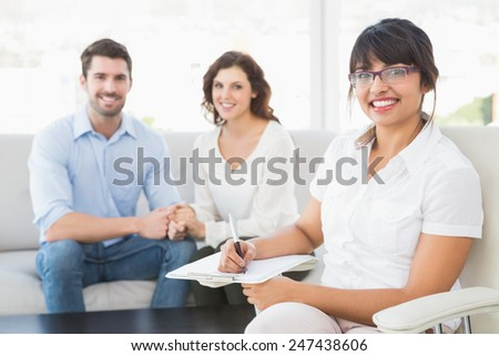 Smiling therapist with patients looking at camera in the office - stock photo