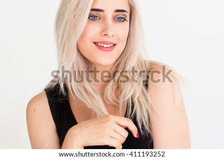 Smiling thoughtful woman with nude makeup on white background. Blonde cheerful tender girl isolated on white. Fashion portrait of young confident girl in light studio. Skin care or hair care concept.  - stock photo