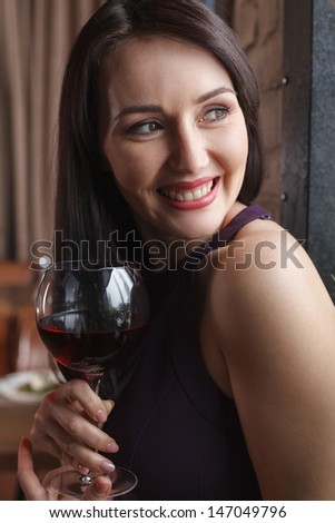 Smiling to him. Beautiful middle-aged women standing with a glass of wine and looking away - stock photo