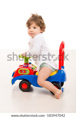 Smiling toddler boy riding a big car toy  and looking camera - stock photo
