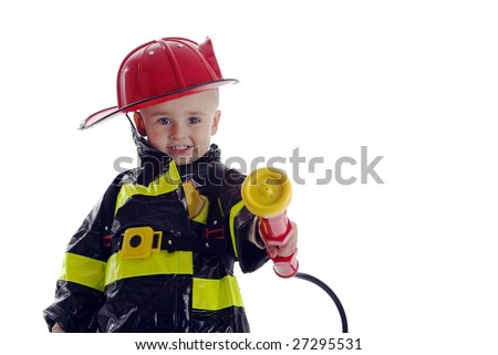 Smiling toddler fire fighter points water sprayer at camera - stock photo
