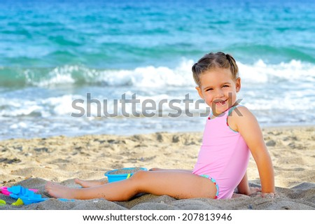 Smiling toddler girl playing with her toys at beach - stock photo