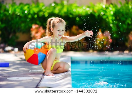 Smiling toddler girl playing with toy in outdoor swimming pool - stock photo