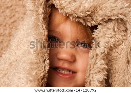 Smiling toddler hiding in fur blanket