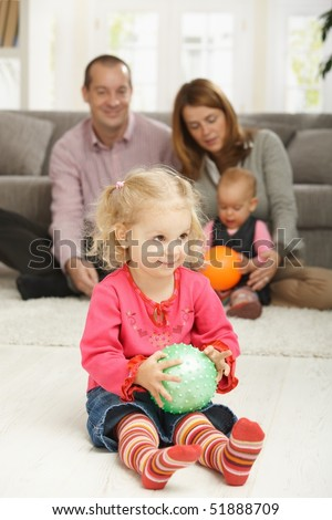 Smiling toddler holding ball with parents and baby in background. - stock photo