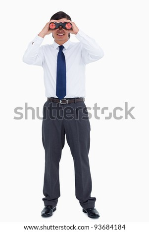 Smiling tradesman looking through spy glass against a white background - stock photo