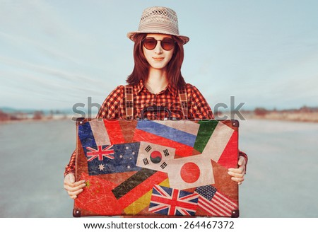 Smiling traveler woman holding suitcase. Stamps flags of different countries on a suitcase. Concept of travel - stock photo