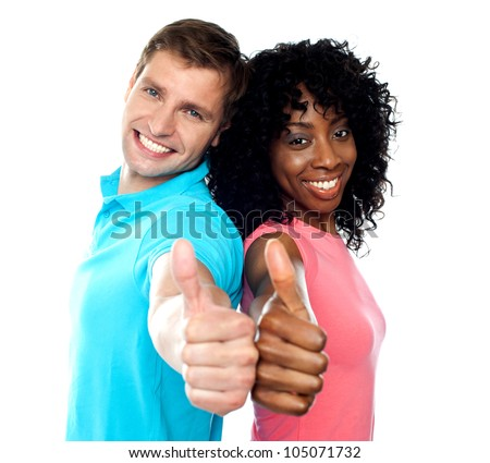 Smiling trendy couple showing thumbs up against white background - stock photo