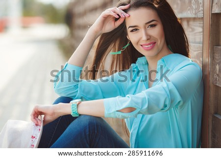 Smiling trendy model posing on wooden background. Attractive young woman enjoying her time outside in park sitting on the ground near wooden fence