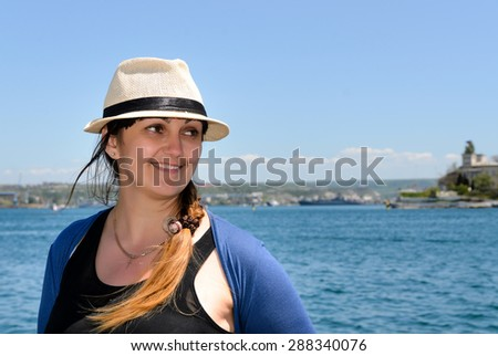 Smiling trendy woman wearing a chic hat with her long hair in a braid enjoying a sunny day at the seaside, head and shoulders portrait