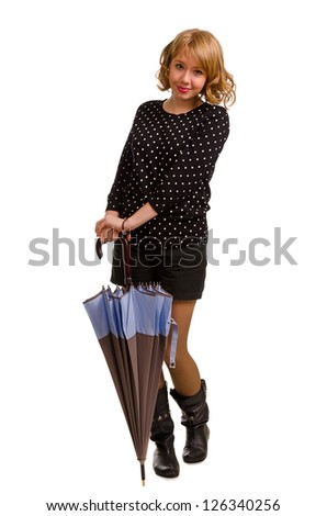 Smiling trendy young blonde woman posing with a closed umbrella in her hands in front of her, full length studio portrait isolated on white - stock photo