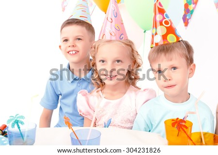 Smiling trio. Two cute little boys and pretty girl sitting at table and posing to camera during birthday party. - stock photo