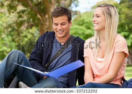 Smiling tutor helping a teenager to revise in a park