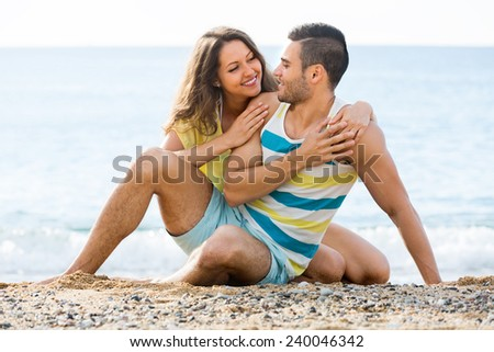 Smiling two having romantic date on sandy beach at sunny day - stock photo