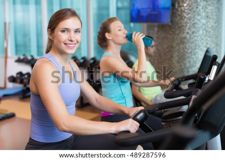 Smiling two women and man cycling in gym