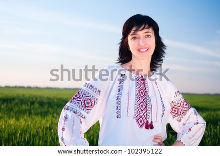 Smiling ukrainian woman outdoors on field  in traditional shirt - stock photo