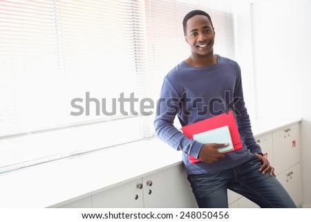 Smiling university student holding notebooks at the university - stock photo