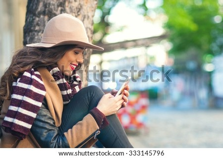 Smiling urban girl uses smart phone with smile on her face on a cold winter day - stock photo