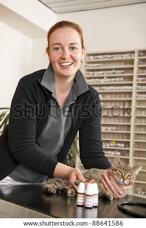 smiling veterinarian looking into camera and holding a cat on the examination table - stock photo