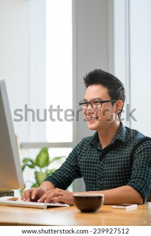 Smiling Vietnamese man working on computer indoors - stock photo
