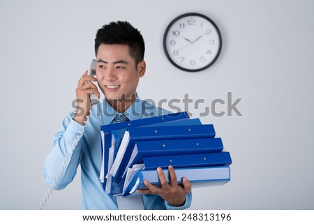 Smiling Vietnamese manager carrying stack of binders and calling on the telephone - stock photo