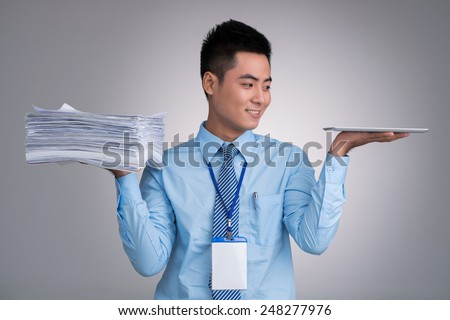 Smiling Vietnamese manager with pile of documents in one hand and digital tablet in another - stock photo