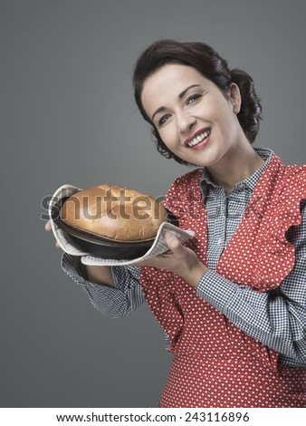 Smiling vintage woman holding an homemade cake in a baking tin - stock photo