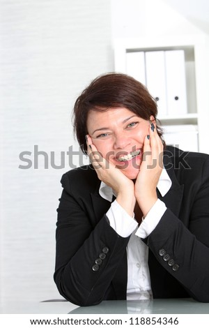 Smiling vivacious businesswoman with a lovely friendly smile sitting at her desk with her chin resting in her hands - stock photo
