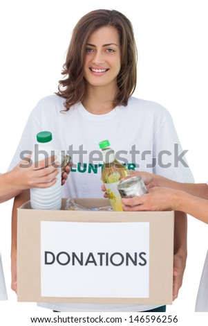 Smiling volunteer holding a food donation box on white background - stock photo