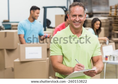Smiling volunteer man taking notes holding clipboard in a large warehouse - stock photo