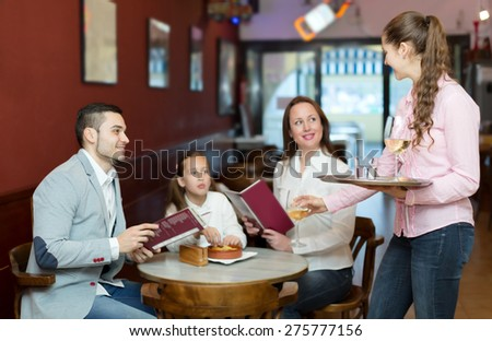 Smiling waitress and cheerful family with daughter reading menu. Focus on the waitress
