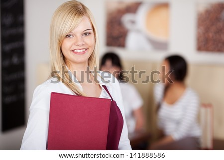 smiling waitress holding menu in cafe with guest in background - stock photo