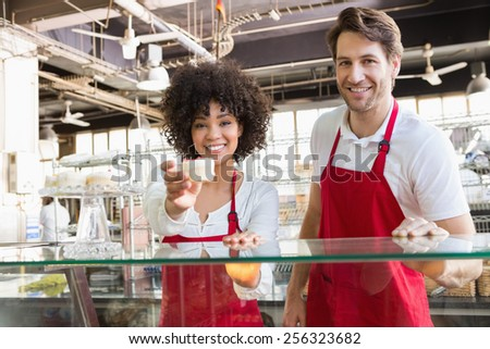 Smiling waitress in red apron offering cupcake at the bakery - stock photo