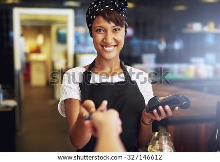 Smiling waitress or small business owner taking a credit card from a customer to process through the banking machine in payment for an order - stock photo