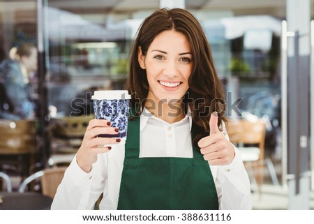 Smiling waitress serving a coffee in cafe - stock photo
