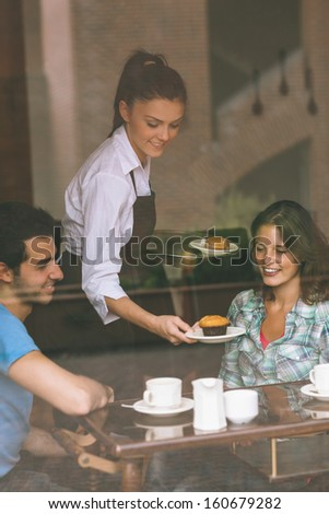 Smiling waitress serving food to a couple in college canteen - stock photo