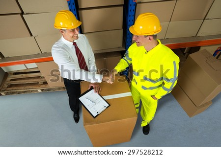 Smiling Warehouse Manager And Worker Shaking Hands In Warehouse - stock photo