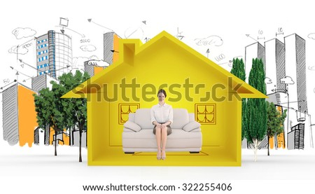 Smiling well dressed woman sitting on sofa against house shape with living room sketch - stock photo