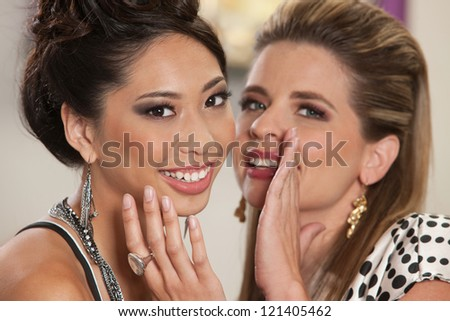 Smiling white female whispering secrets to her Asian friend - stock photo