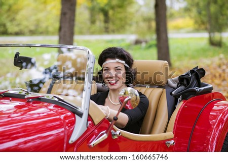 Smiling widely young woman after red car wheel