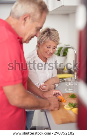 Smiling Wife Watching Over her Husband While Slicing the Fresh Food Ingredients for their Dinner at the Kitchen. - stock photo