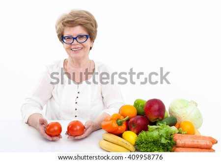 Smiling woman a pensioner with two tomatoes in hands sitting near fresh fruit and vegetables, white background - stock photo