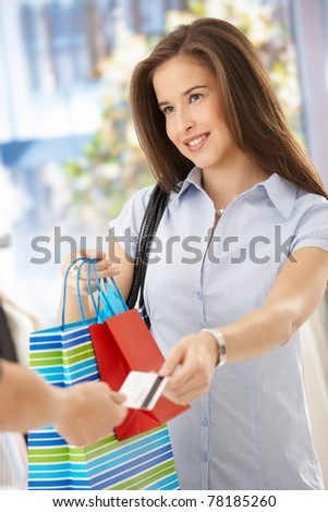 Smiling woman after shopping, taking shopping bags and credit card.? - stock photo