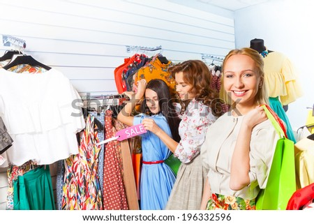 Smiling woman and her friends in shop together