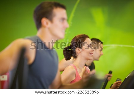 Smiling woman and two men working out at the gym - stock photo